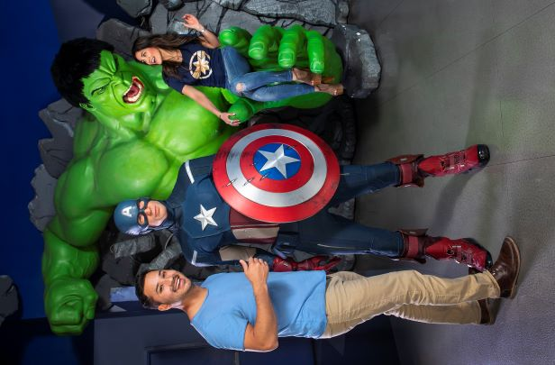 two people taking a picture with Marvel characters