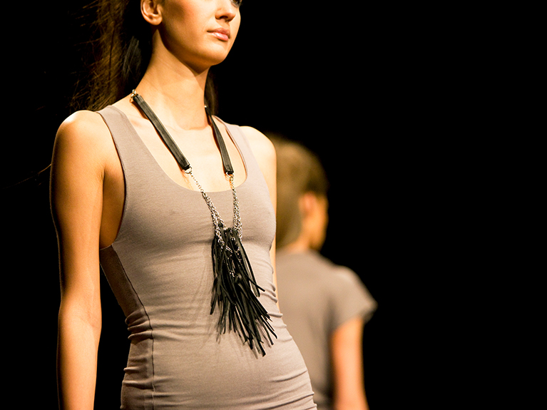 A model walking down a runway in fashionable attire