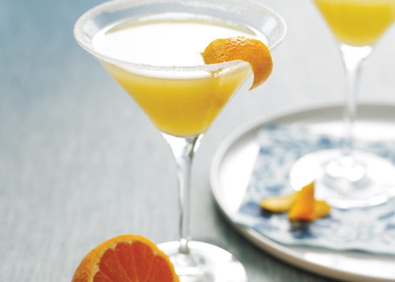 A filled martini glass with an orange peel garnish