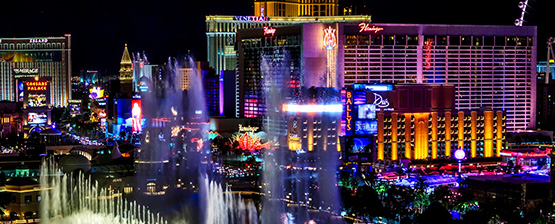 Vegas strip lit up at night with the Bellagio fountain running