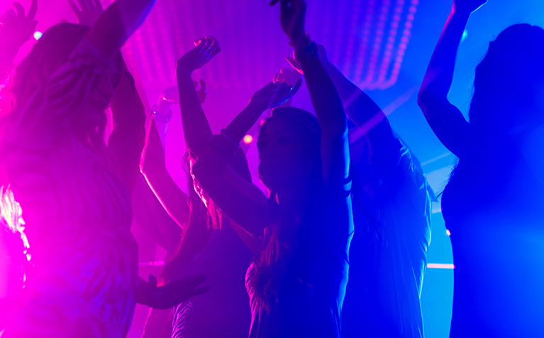 A group of people dancing with bright uplights in the background